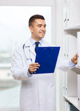 Happy doctor with clipboard in medical office Royalty Free Stock Photo