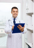 Happy doctor with clipboard in medical office Stock Photography