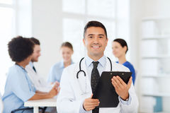 Happy doctor with clipboard over medical team Stock Photos