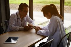 Happy doctor couple playing smartphone. Two happy doctor couple playing smartphone and relaxing at clear wooden table with tablet pc near restaurant window. 4g Royalty Free Stock Images
