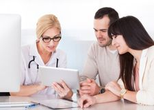 Happy doctor discussing with couple Stock Image