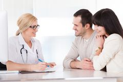 Happy doctor discussing with couple Royalty Free Stock Photos