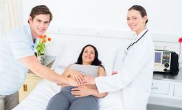 Happy doctor and expectant couple Royalty Free Stock Images