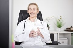 Happy Doctor on her Chair with a Cup of Coffee Stock Image