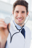 Happy doctor with his stethoscope looking at camera Stock Image