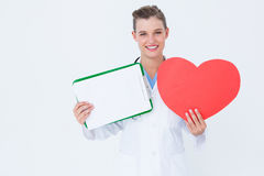Happy doctor holding clipboard and heart card Stock Photo