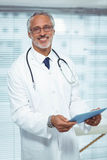 Happy doctor holding clipboard stock photos