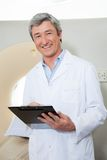 Happy Doctor Holding Clipboard. Portrait of happy mature male doctor holding clipboard while standing next to CT scan machine Royalty Free Stock Photography