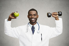 Happy doctor holding green apple, dumbbell Stock Photos