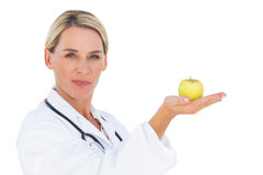 Happy doctor holding out green apple and looking at camera Royalty Free Stock Image