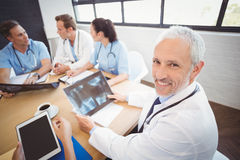 Happy doctor holding a x-ray report in conference room. Portrait of happy doctor holding a x-ray report in conference room in hospital and colleagues discussing Stock Photos