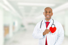 Happy doctor holding red heart standing in hospital hallway Royalty Free Stock Photography