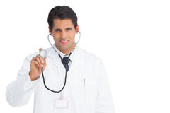 Happy doctor holding up stethoscope Royalty Free Stock Photos