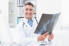 Happy doctor holding x-ray in clinic Royalty Free Stock Image