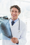 Happy doctor holding X-ray and smiling at camera Stock Photos