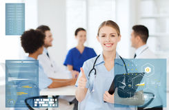 Happy doctor at hospital showing thumbs up gesture Stock Photo