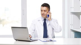 Happy doctor with laptop calling on smartphone stock video