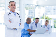 Happy doctor looking at camera with arms crossed while his colleagues works Stock Images