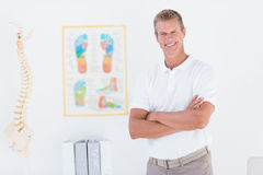 Happy doctor looking at camera with arms crossed Stock Photo