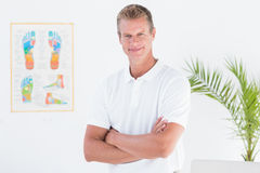 Happy doctor looking at camera with arms crossed Stock Image