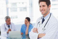 Happy doctor looking at camera with colleagues behind Royalty Free Stock Image