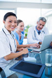 Happy doctor looking at camera while colleagues are talking Stock Images