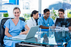 Happy doctor looking at camera while her colleagues looks at Xray Royalty Free Stock Photography