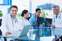 Happy doctor looking at camera while his colleagues looks at Xray Royalty Free Stock Image