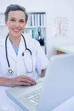Happy doctor looking at camera and using her smartphone Royalty Free Stock Photos
