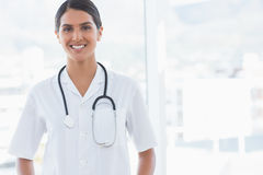 Happy doctor looking at camera beside windows Stock Photo