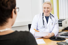 Happy Doctor Looking At Female Patient At Desk. Happy mature doctor looking at female patient at desk in clinic royalty free stock images