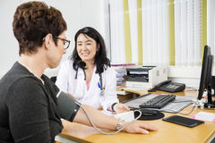 Happy Doctor Looking At Patient While Examining Her Blood Pressu Stock Photos