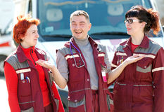 Happy doctor man gesturing with smiling paramedics coworker colleague. Happy doctor men gesturing with smiling paramedics coworker colleague on ambulance vehicle Stock Images