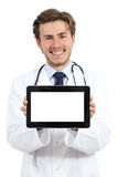 Happy doctor man showing a blank tablet screen software. On a white background Royalty Free Stock Image