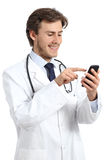 Happy doctor man texting on a smart phone Royalty Free Stock Images