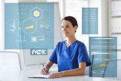 Happy doctor or nurse with clipboard at hospital stock photos