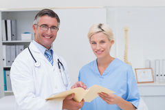 Happy doctor and nurse holding report Stock Image