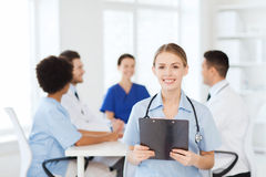 Happy doctor over group of medics at hospital Royalty Free Stock Photography