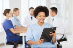 Happy doctor over group of medics at hospital Stock Photography