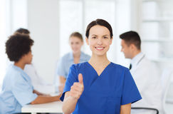 Happy doctor over group of medics at hospital Stock Photos