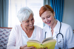 Happy doctor and patient reading a book. At home Royalty Free Stock Images