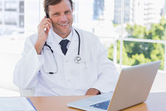 Happy doctor phoning in his office Royalty Free Stock Photo