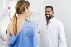 Happy Doctor Preparing Patient For Mammogram Test. Happy male doctor preparing female patient for mammogram X-ray test in hospital Stock Image