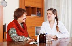 Happy  doctor prescribing medication to senior woman Stock Images