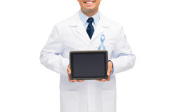 Happy doctor with prostate cancer awareness ribbon Stock Photography