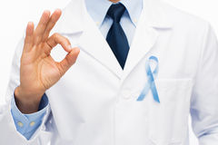 Happy doctor with prostate cancer awareness ribbon. Healthcare, profession, people, gesture and medicine concept - close up of male doctor in white coat with sky royalty free stock photo