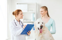 Happy doctor with retriever dog at vet clinic Stock Photography