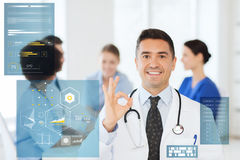 Happy doctor showing ok hand sign at hospital Stock Image