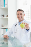 Happy doctor sitting at his desk Royalty Free Stock Image