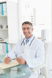 Happy doctor sitting at his desk Stock Photo
